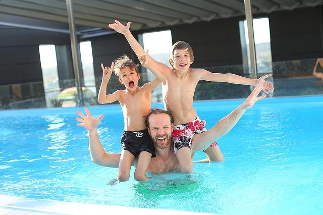 děti a dospělý muž v bazénu