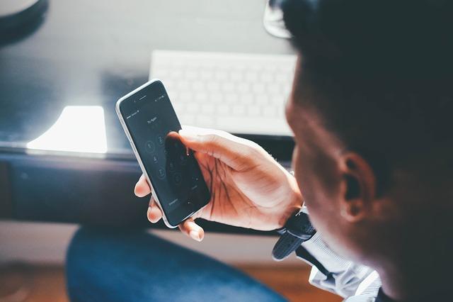 muž sledující svůj telefon